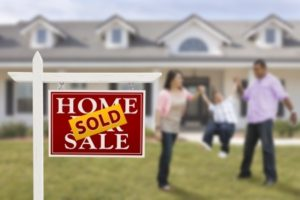 sold real estate sign and playful hispanic family in front of house.